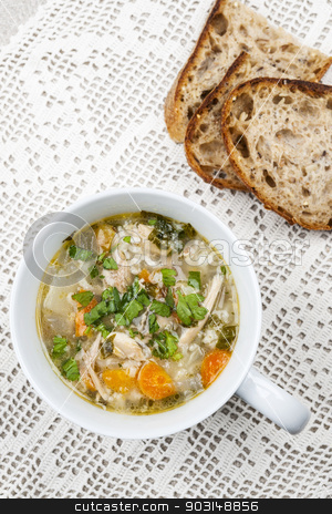 Cup of chicken soup stock photo, Cup of hot chicken rice soup served with bread from above on crochet tablecloth by Elena Elisseeva