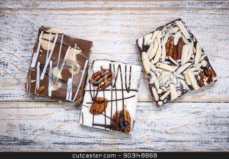 Chocolate caramel bark pieces stock photo, Three assorted chocolate caramel bark pieces as sweet dessert arranged on wooden background from above by Elena Elisseeva