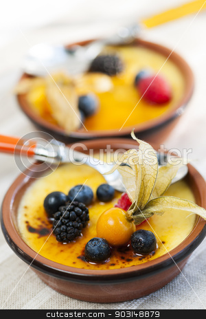 Creme brulee dessert stock photo, Sweet creme brulee desserts topped with fresh berries by Elena Elisseeva