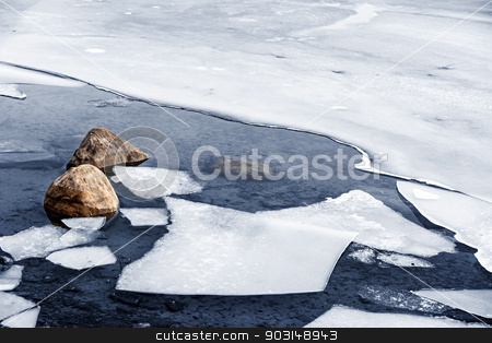 Icy shore in winter stock photo, Broken ice floating on water at cold lake shore with rocks in winter by Elena Elisseeva