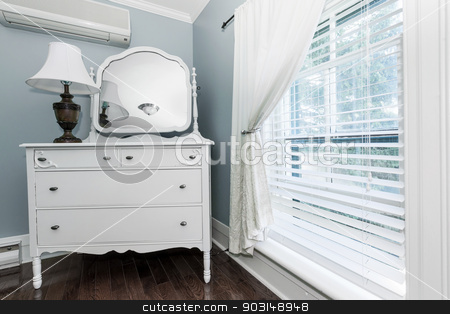 Cottage dresser with mirror stock photo, White painted dresser with mirror and lamp near window interior by Elena Elisseeva