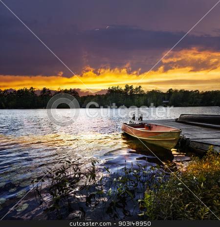 Boat docked on lake at sunset stock photo, Rowboat tied to dock on beautiful lake with dramatic sunset by Elena Elisseeva