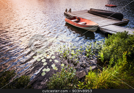 Rowboat at lake shore at sunrise stock photo, Sunset reflecting in lake water with rowboat tied to wooden dock at rocky shore. Ontario, Canada. by Elena Elisseeva
