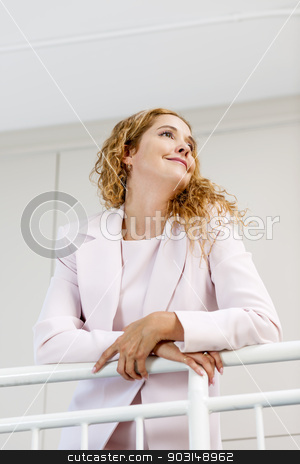 Portrait of confident businesswoman in office stock photo, Profile of confident successful business woman standing in office hallway leaning on railing shot from below by Elena Elisseeva