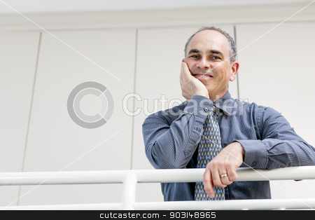 Happy businessman standing in hallway stock photo, Portrait of smiling proud business man standing in office hallway leaning on railing with copy space by Elena Elisseeva