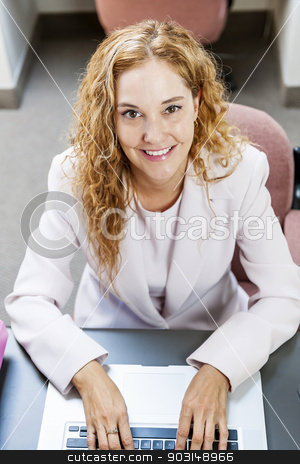 Woman typing on laptop computer in office at work stock photo, Smiling businesswoman sitting at workstation in office with computer by Elena Elisseeva