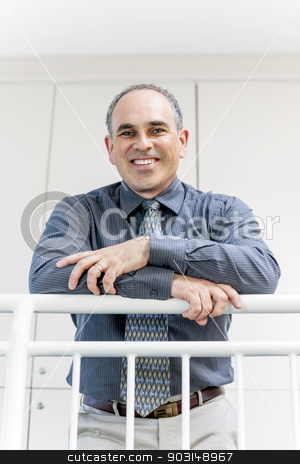 Businessman standing in office hallway smiling stock photo, Portrait of smiling proud business man standing in office hallway leaning on railing by Elena Elisseeva