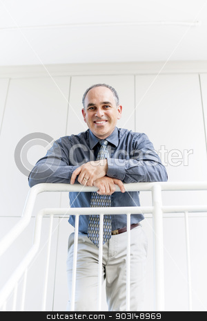 Portrait of successful happy businessman in office stock photo, Smiling proud business man standing in office hallway leaning on railing by Elena Elisseeva