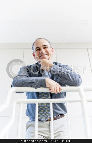 Portrait of successful happy businessman in office stock photo, Smiling proud business man standing in office hallway leaning on railing shot from below by Elena Elisseeva