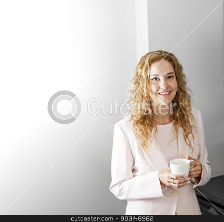 Businesswoman with coffee stock photo, Business woman in suit standing and holding coffee cup on break with copy space by Elena Elisseeva