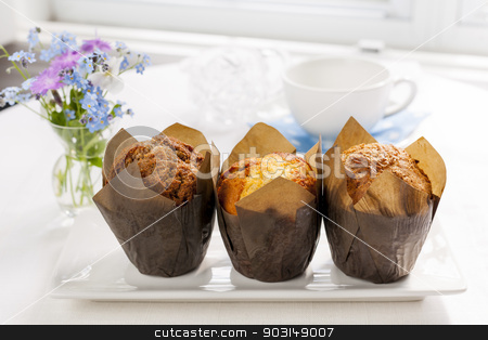 Muffins for breakfast stock photo, Breakfast table with three muffins in brown paper baking cups by Elena Elisseeva