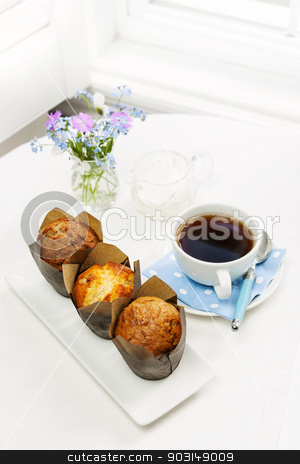 Muffins and coffee for breakfast stock photo, Three muffins and cup of coffee on breakfast table in the morning by Elena Elisseeva