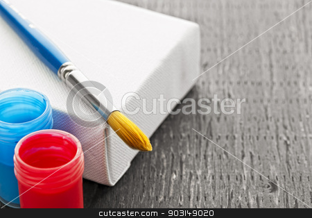 Paintbrush on canvas stock photo, Paintbrush on white blank canvas with red and blue paints by Elena Elisseeva