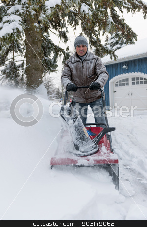Man clearing driveway with snowblower stock photo, Man using snowblower to clear deep snow on driveway near residential house after heavy snowfall. by Elena Elisseeva