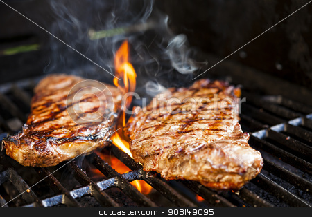 Steaks on barbecue stock photo, Beef steaks cooking in open flame on barbecue grill by Elena Elisseeva