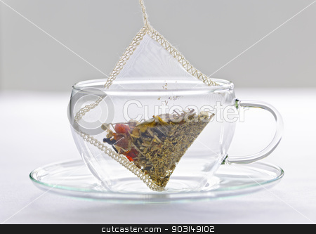 Herbal tea bag in glass cup stock photo, Glass teacup with soothing herbal tea in silk bag by Elena Elisseeva