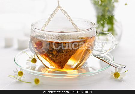 Herbal tea in glass cup stock photo, Glass teacup with soothing herbal tea in silk bag by Elena Elisseeva