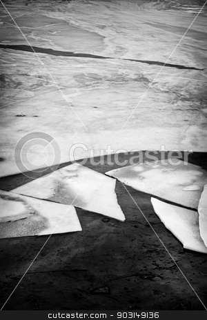 Broken ice stock photo, Black and white image of broken ice pieces in dark water by Elena Elisseeva