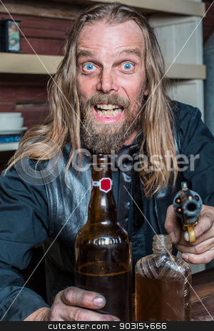 Crazed Western Man at Table stock photo, Crazed Western Man Aims Gun Towards You as he Sits at Table by Scott Griessel