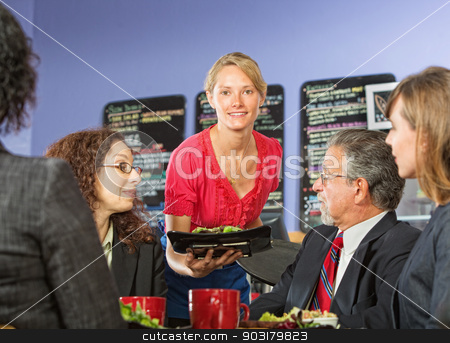 Woman Serving Lunch stock photo, Pretty young server bringing food to group of business people by Scott Griessel