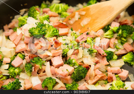 Pan of Chopped Onions Ham and Broccoli stock photo, A stir fry of chopped ham, broccoli and onions in a frying pan with wood spoon by Darryl Brooks