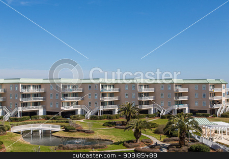 Coastal Condos with Balconies Under Blue Sky stock photo, A nice beach condo resort with landscaping by Darryl Brooks