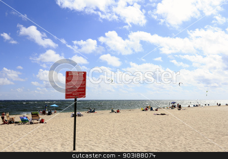Designated Water Sport Area stock photo, POMPANO BEACH, FLORIDA - FEBRUARY 12, 2014: On the beach with many people and a few kite boarders off the coast a red and white sign showing designated water sports area with rules for recreation.  by Lee Serenethos