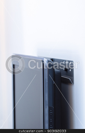 Display attached to wall mount support stock photo, LCD / Plasma / Monitor wall mount with a modern unit attached to a white wall. Subtle blue technological color cast by ifeelstock