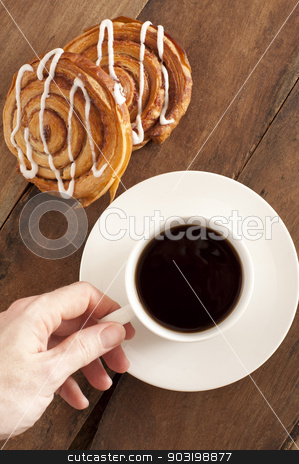 Coffee and fresh Danish for breakfast stock photo, Overhead view of a mans hand reaching out to take a cup of rich espresso coffee and fresh Danish pastries for breakfast by Stephen Gibson