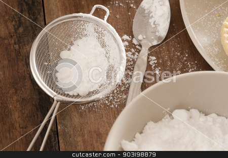 Kitchen sieve filled with icing sugar stock photo, Kitchen sieve filled with icing sugar lying on a wooden kitchen counter alongside a mixing bowl while baking or cooking pastries and food by Stephen Gibson