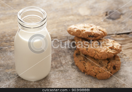 Fresh milk and cookies stock photo, Childhood treat of a glass bottle of fresh milk served with crunchy cookies for a delicious snack by Stephen Gibson