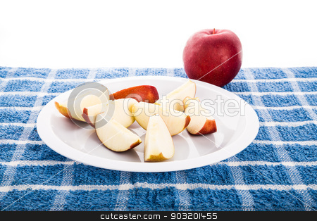 Red Apple with Slices on White Plate stock photo, Cut up apple on a white plate on blue towel with a whole red apple against white background by Darryl Brooks