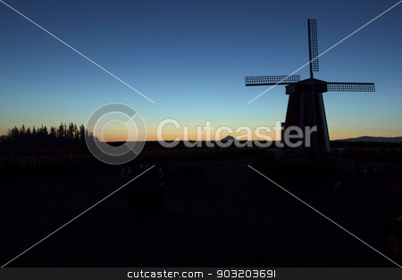 Silhouette of Windmill at Sunrise stock photo, Silhouette of Windmill with Mt Hood in the Distance at Tulip Field in Woodburn Oregon During Sunrise by Jit Lim