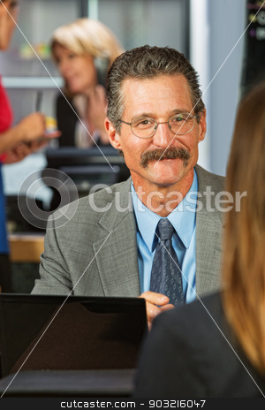 Business Man Talking with Woman stock photo, Cheerful businessman with eyeglasses and mustache with woman in cafe by Scott Griessel