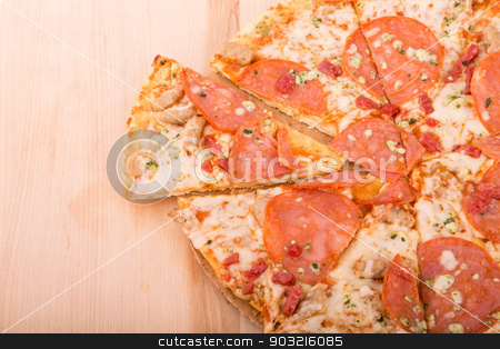 Sliced Pepperoni Pizza on Wood Cutting Board with Copy Space stock photo, Ahot cheesy pepperoni pizza on a wood cutting board with room for copy space by Darryl Brooks