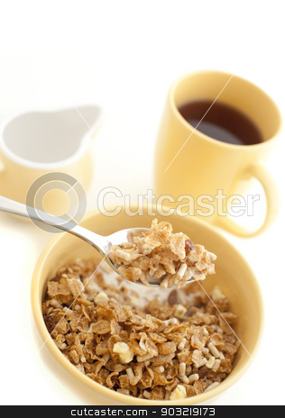 Bowl of healthy muesli for breakfast stock photo, Eating a bowl of healthy muesli for breakfast with a mouthful raised on a spoon and a mug of coffee in the background by Stephen Gibson
