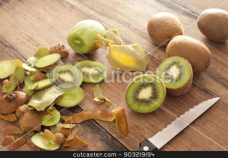 Peeling and slicing kiwifruit for dessert stock photo, Peeling and slicing fresh tropical kiwifruit for dessert with whole and halved fruit and peels lying on a wooden kitchen counter with a knife by Stephen Gibson