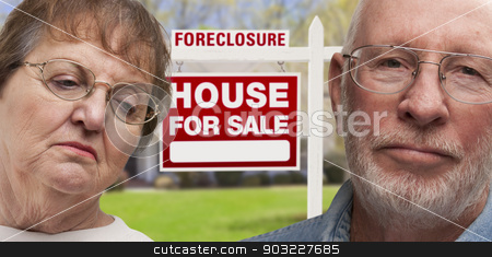Depressed Senior Couple in Front of Foreclosure Sign and House stock photo, Depressed Senior Couple in Front of Foreclosure Real Estate Sign and House. by Andy Dean