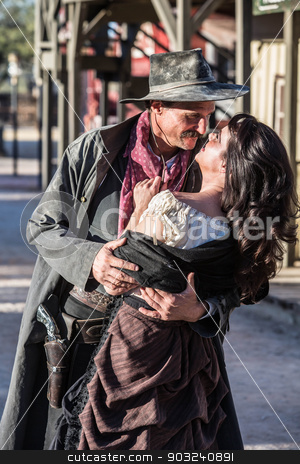 Gruff Man and Woman Kiss stock photo, Portrait of an old west woman and sheriff kissing by Scott Griessel