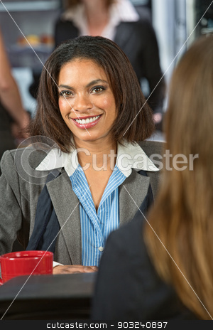 Smiling Young Woman stock photo, Smiling Black woman talking with friend in cafeteria by Scott Griessel