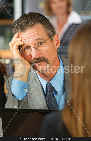 Sad Businessman stock photo, Sad businessman listening to woman in cafe by Scott Griessel