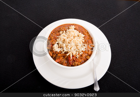 Chili Over Rice stock photo, A white bowl of chili con carne with beans served over rice on a black background by Darryl Brooks