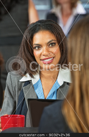 Woman Talking with Coworker stock photo, Smiling Hispanic female business woman talking with coworker in cafeteria by Scott Griessel