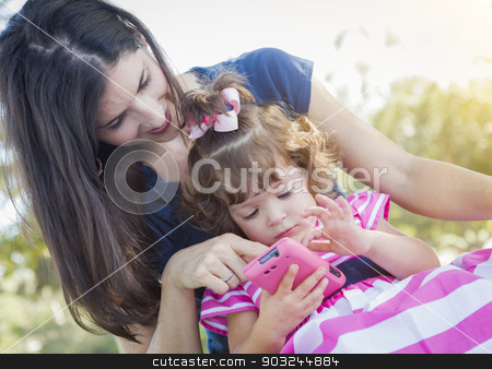 Mother and Cute Baby Daughter Playing with Cell Phone stock photo, Mixed Race Mother and Cute Baby Daughter Playing with Cell Phone in Park. by Andy Dean