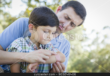 Loving Father Puts Bandage on Elbow of Young Son stock photo, Loving Father Puts a Bandage on the Elbow of His Young Son in the Park. by Andy Dean