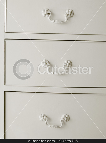 White drawers with old fashioned handles  stock photo, White drawers with old fashioned handles. Vertical by ABBPhoto