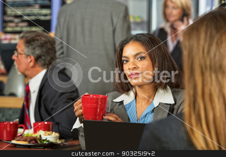 Woman Listening to Coworker stock photo, Young African woman listening to coworker in a cafe by Scott Griessel