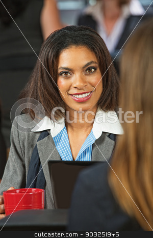 Smiling Female Executive stock photo, Grinning female executive holding coffee and talking with friend by Scott Griessel