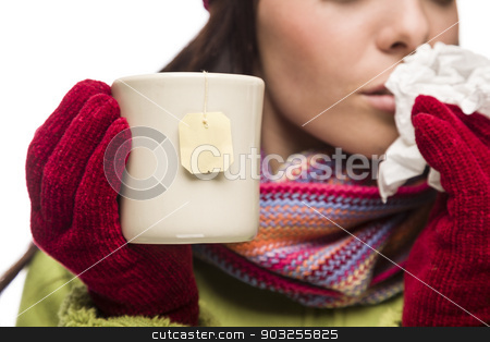 Young Sick Woman Holding Cup with Blank Tea Bag Hanging stock photo, Young Sick Woman with Tissue Holding Cup with Blank Tea Bag Hanging. by Andy Dean