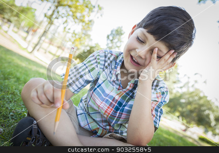 Frustrated Cute Young Boy Holding Pencil Sitting on the Grass stock photo, Frustrated Cute Young Boy Holding Pencil Sitting on the Grass Outdoors. by Andy Dean